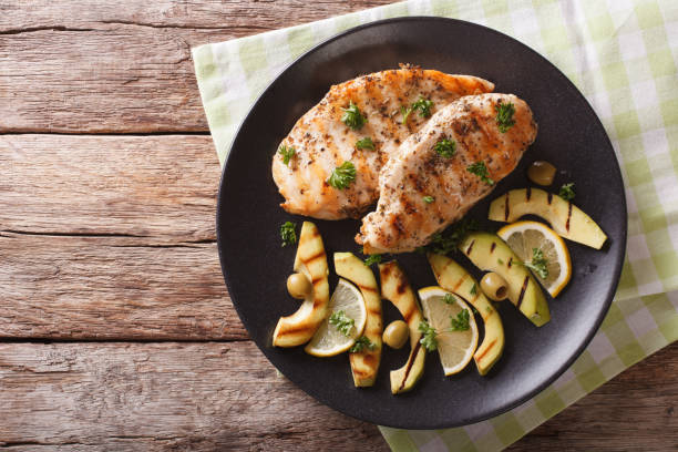 Grilled chicken breast with avocado, lemon and olive close-up. horizontal top view stock photo