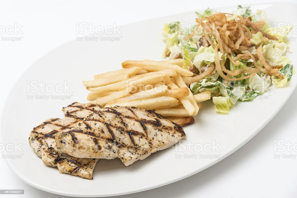 A grilled chicken breast with Caesar salad and fries. royalty-free stock photo