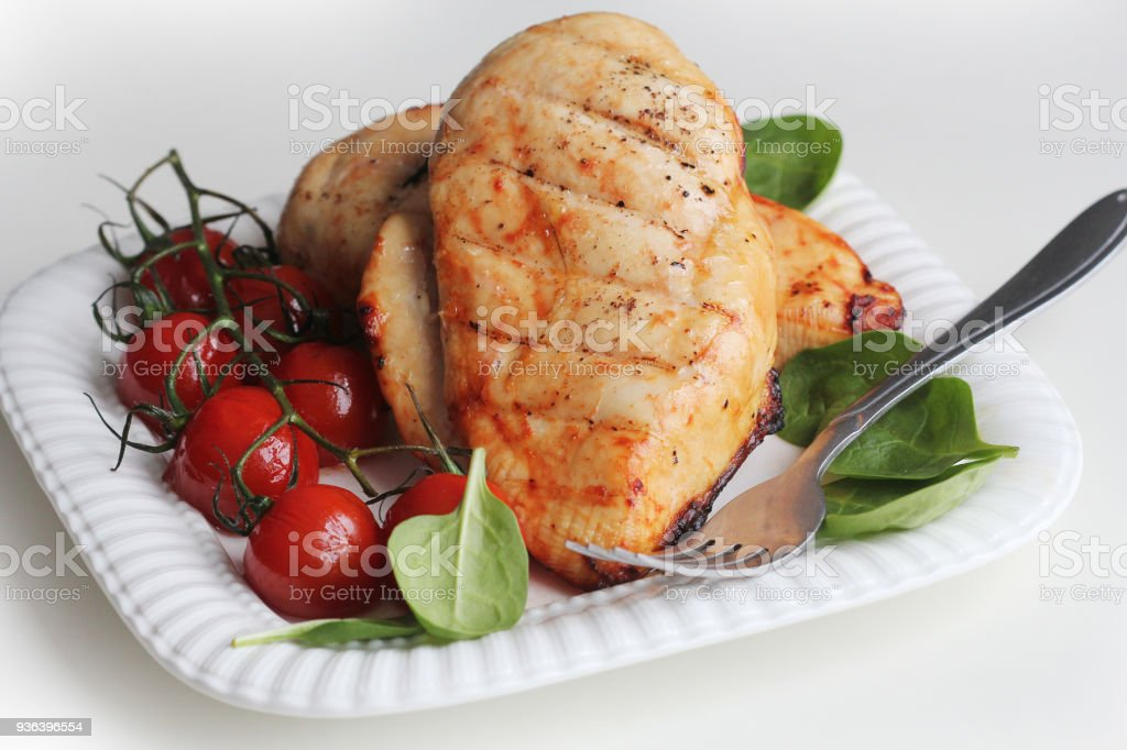 Grilled chicken breast with cherry tomatoes, spinach on a white plate stock photo