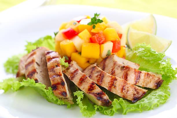 Grilled chicken breast with fresh mango salsa, soft focus stock photo