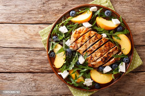 Grilled chicken breast with fresh peaches, blueberries, arugula and feta cheese close-up on a plate on a table. Horizontal top view from above