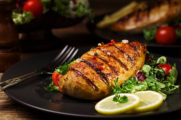 grilled chicken breast with green salad and french fries. stock photo