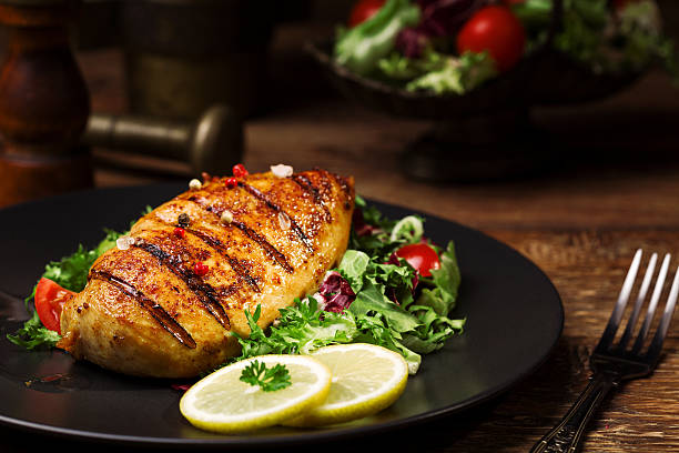 grilled chicken breast with green salad and french fries. grilled chicken breast with green salad and french fries on a black plate. grilled chicken breast stock pictures, royalty-free photos & images