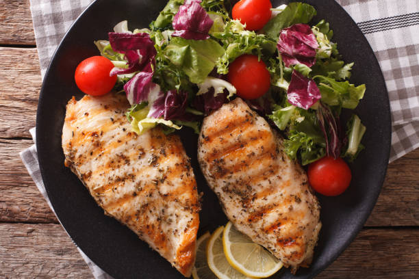 Grilled chicken breast with mixed salad close-up. horizontal top view Grilled chicken breast with mixed salad on a plate close-up. horizontal view from above chicken breast stock pictures, royalty-free photos & images