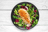 grilled chicken breast with mixed salad on a black plate. top view