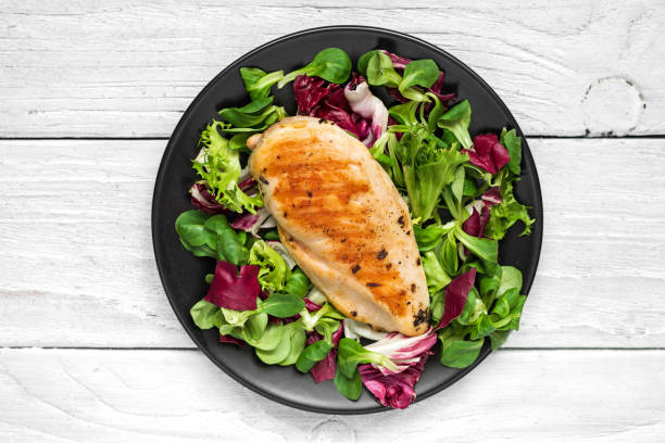 grilled chicken breast with mixed salad on a black plate with knife and fork - chicken meat stock pictures, royalty-free photos & images