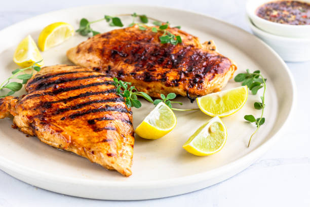 """Grilled Chicken Breast with Oregano and Lemon Grilled Chicken Breast with Fresh Herb and Lemon  Directly Above Photo. Cooked Chicken Breast in a White Plate """"nand on White Background. grilled chicken breast stock pictures, royalty-free photos & images"""