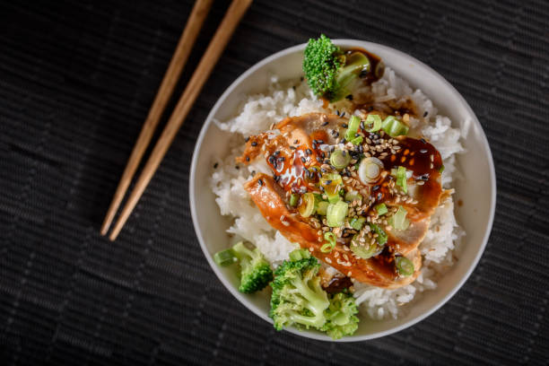 照り焼き蒸しご飯の上に鶏胸肉のグリル - 丼物 ストックフォトと画像