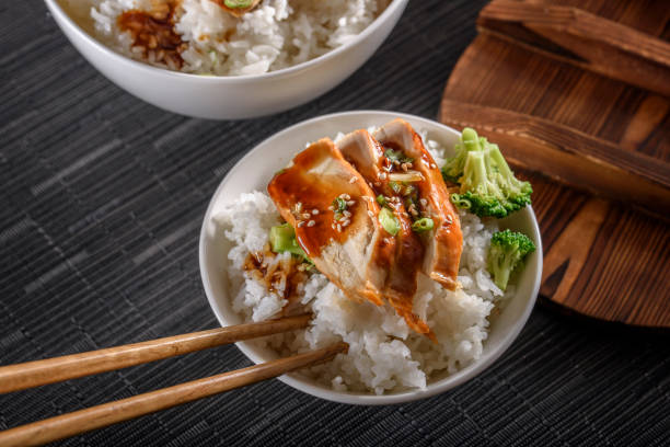 Grilled Chicken Breast with Teriyaki Sauce over Steamed Rice stock photo