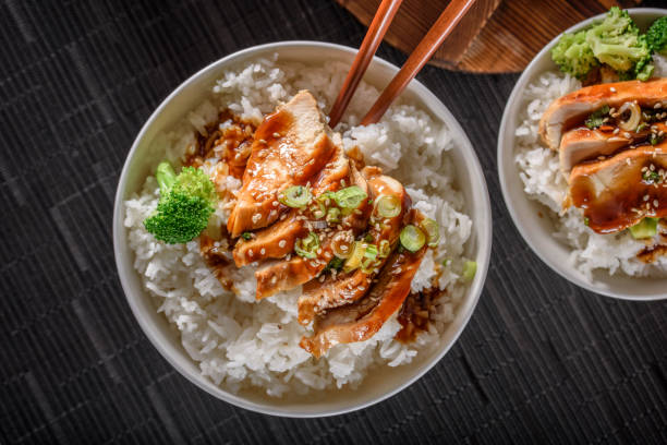 grilled chicken breast with teriyaki sauce over steamed rice - chicken rice stock photos and pictures
