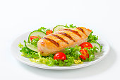 fillet of grilled chicken breasts with vegetable garnish on a white plate