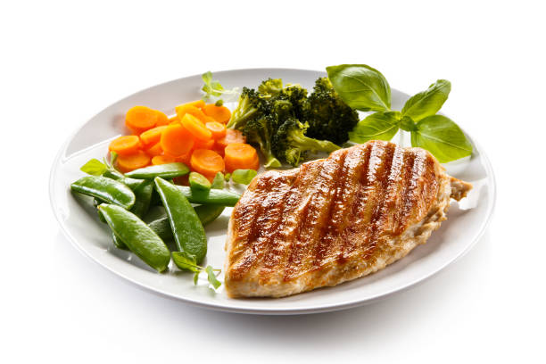 Grilled chicken breast with vegetable salad on white background