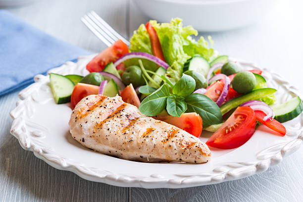 grilled chicken breast with vegetable salad - serving size stock photos and pictures