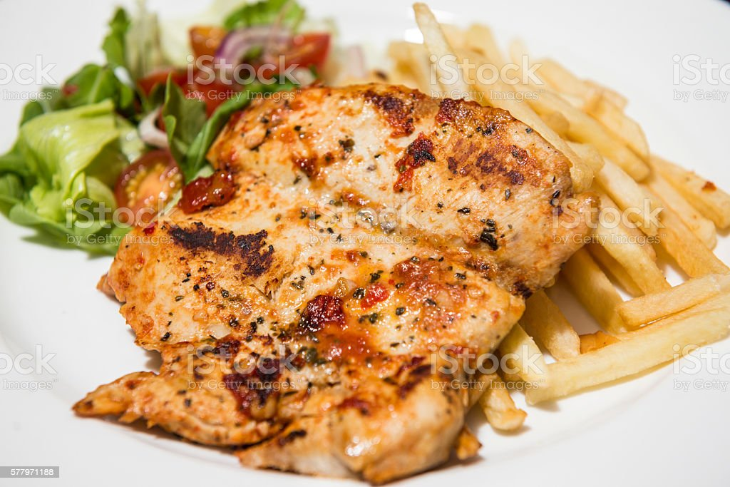 Grilled chicken breast with vegetables and chips stock photo