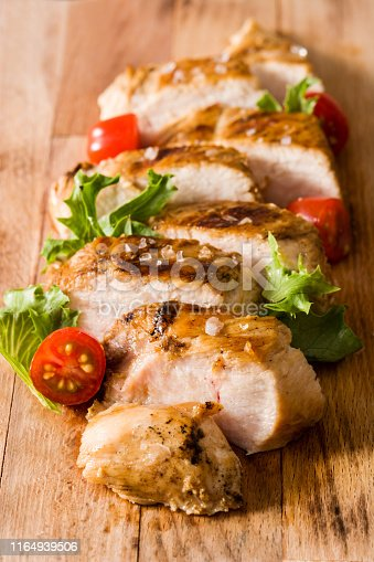 Grilled chicken breast with vegetables on wooden table. Close up