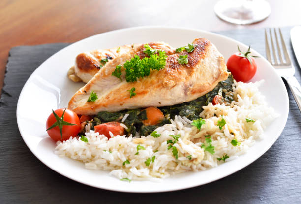 grilled chicken breast with vegetables, rice and cherry tomatoes - chicken rice stock photos and pictures