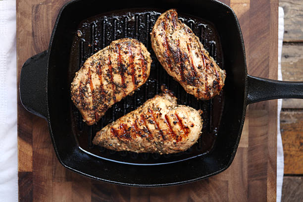 """Grilled chicken breasts """"Healthy eating:  grilled skinless, boneless chicken breasts in a cast iron grilling pan."""" grilled chicken breast stock pictures, royalty-free photos & images"""