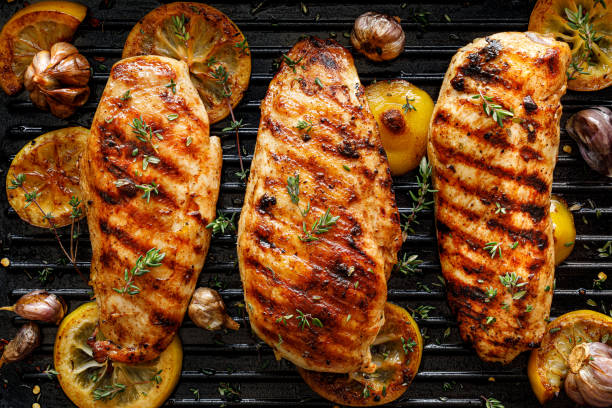 Grilled chicken breasts with thyme, garlic and lemon slices on a grill pan close up Grilled chicken breasts with thyme, garlic and lemon slices on a grill pan close up, top view cooked stock pictures, royalty-free photos & images