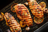 istock Grilled chicken breasts with thyme, garlic and lemon slices on a grill pan close up 1217760999
