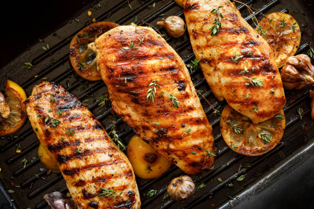 Grilled chicken breasts with thyme, garlic and lemon slices on a grill pan close up Grilled chicken breasts with thyme, garlic and lemon slices on a grill pan close up, top view grilled chicken breast stock pictures, royalty-free photos & images