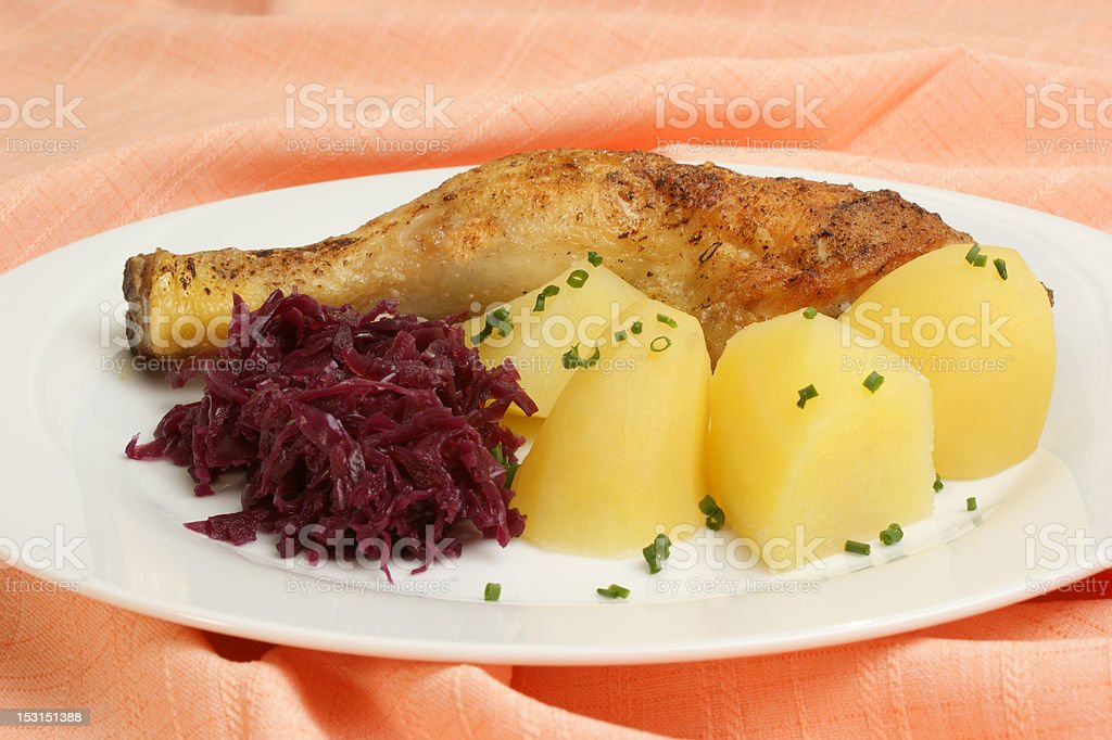 Grilled chicken drumstick with potatoes and red cabbage royalty-free stock photo