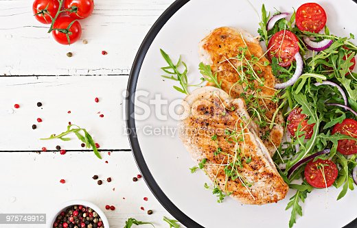 646207652istockphoto Grilled chicken fillet and fresh vegetable salad of tomatoes,red onion and arugula. Chicken meat salad. Healthy food. Flat lay. Top view. 975749912
