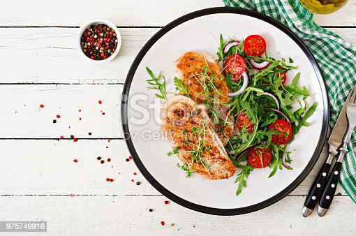 646207652istockphoto Grilled chicken fillet and fresh vegetable salad of tomatoes,red onion and arugula. Chicken meat salad. Healthy food. Flat lay. Top view. 975749916