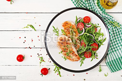 646207652istockphoto Grilled chicken fillet and fresh vegetable salad of tomatoes,red onion and arugula. Chicken meat salad. Healthy food. Flat lay. Top view. 975749934