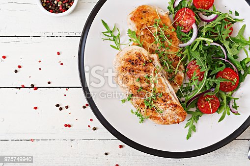 646207652istockphoto Grilled chicken fillet and fresh vegetable salad of tomatoes,red onion and arugula. Chicken meat salad. Healthy food. Flat lay. Top view. 975749940