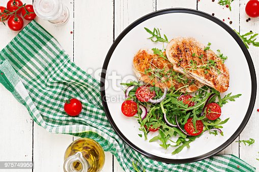 646207652istockphoto Grilled chicken fillet and fresh vegetable salad of tomatoes,red onion and arugula. Chicken meat salad. Healthy food. Flat lay. Top view. 975749950