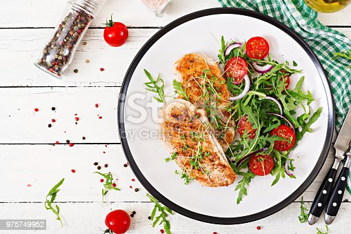 646207652istockphoto Grilled chicken fillet and fresh vegetable salad of tomatoes,red onion and arugula. Chicken meat salad. Healthy food. Flat lay. Top view. 975749952