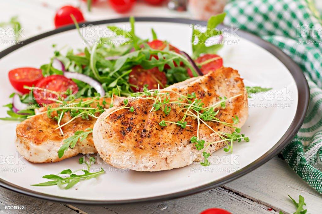 Gegrilltes Hühnerfilet und frischem Salat aus Tomaten, roten Zwiebeln und Rucola. Hähnchen-Fleisch-Salat. Gesunde Ernährung. - Lizenzfrei Bratengericht Stock-Foto