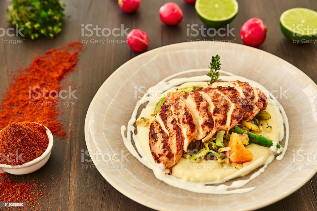 Grilled chicken fillet is cut into slices on a cushion of mashed potatoes with vegetables - onion, garlic, pepper, cabbage, radish, greens in a large beige dish on a dark wooden table. stock photo