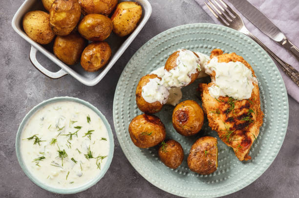 Grilled chicken fillet with baked potatoes and garlic yogurt dip. stock photo