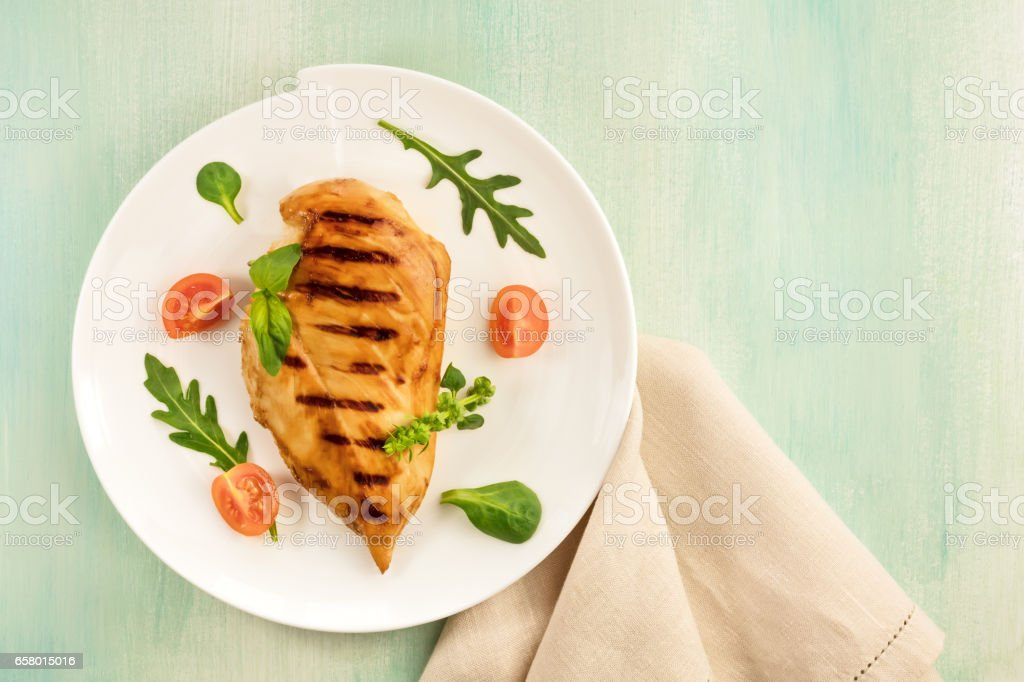 Grilled chicken fillet with cherry tomatoes and salad leaves stock photo