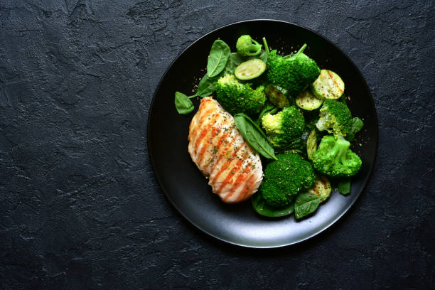 Grilled chicken fillet with green vegetable salad Grilled chicken fillet with green vegetable salad on a black slate, stone or concrete background.Top view with copy space. broccoli stock pictures, royalty-free photos & images