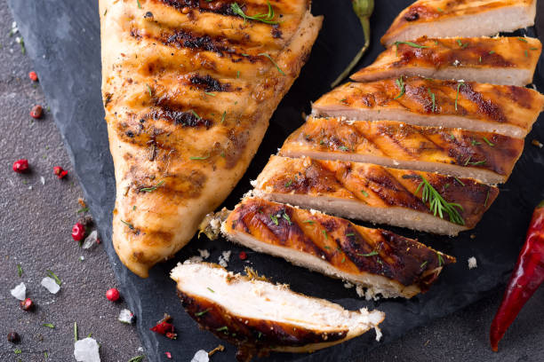 Grilled chicken fillets on slate plate on Gray concrete background. Healthy diet food concept, flat lay close up Grilled chicken fillets on slate plate on Gray concrete background. Healthy diet food concept grilled chicken breast stock pictures, royalty-free photos & images