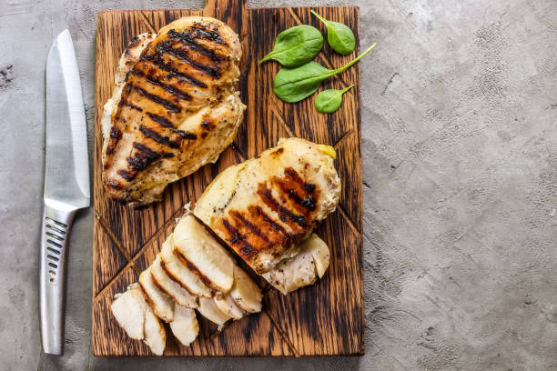grilled chicken fillets on wooden cutting board stock photo