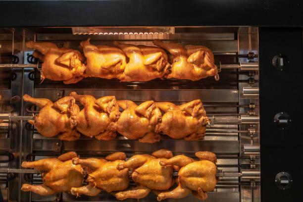 grilled chicken in a grill - girarrosto foto e immagini stock