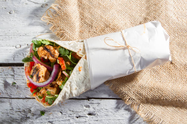 grelhado frango kebab doner envolvê-com cebola, salsa e tomate na rústica mesa de madeira pintada branca. - cilindro - fotografias e filmes do acervo