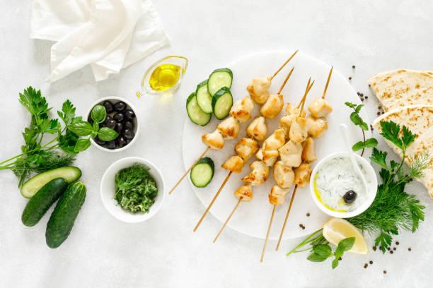 Gegrillter Hähnchenkebab auf Spießen und traditionelle griechische Tzatziki-Joghurtsauce, Blick von oben – Foto