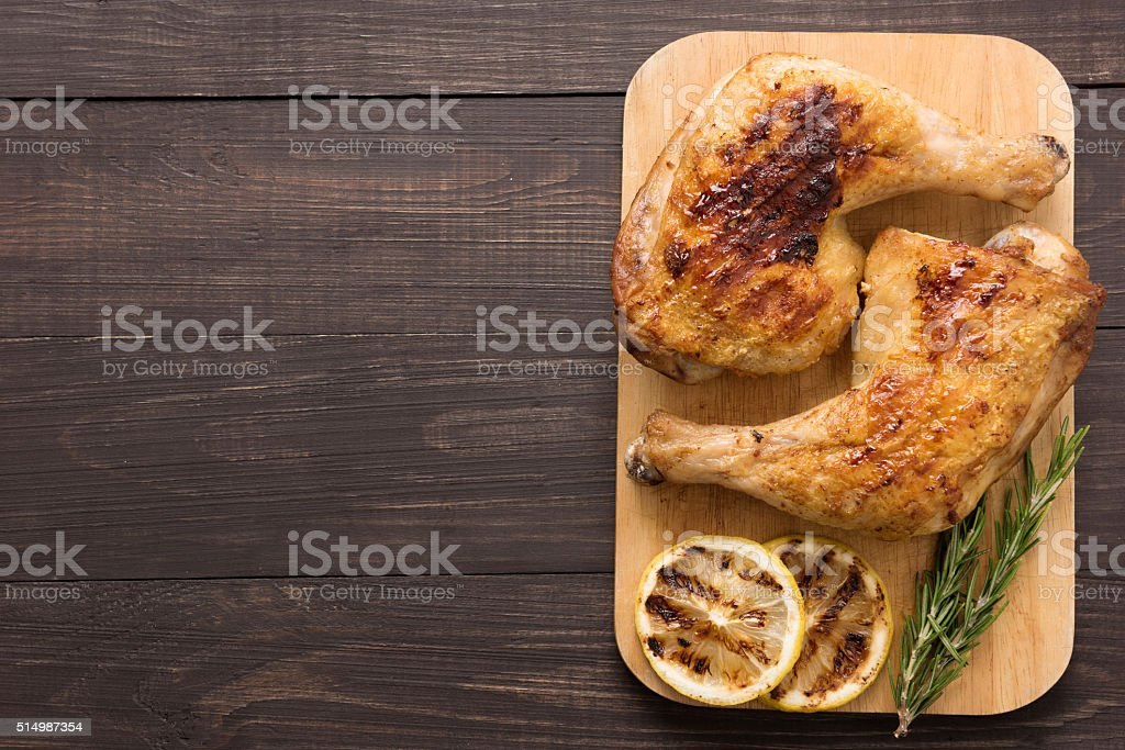 Grilled chicken lag and rosemary on wooden background stock photo