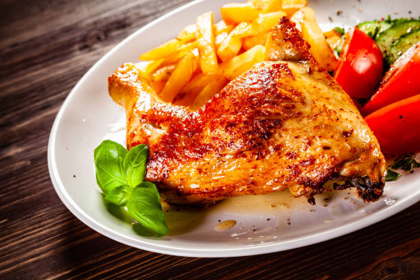 Grilled chicken leg with french fries and vegetables on timber background stock photo