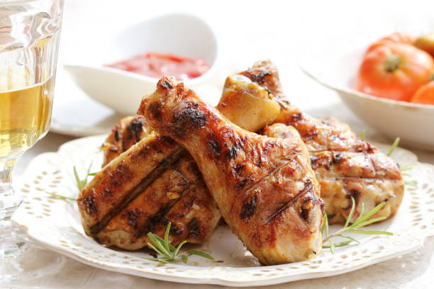 Grilled chicken legs with rosemary on table stock photo