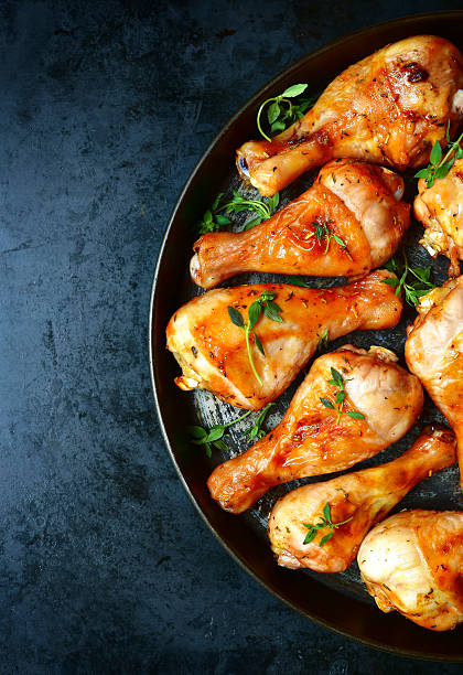 Grilled chicken legs with thyme. Grilled chicken legs with thyme on a black tray.Copy space background.Top view drumstick stock pictures, royalty-free photos & images