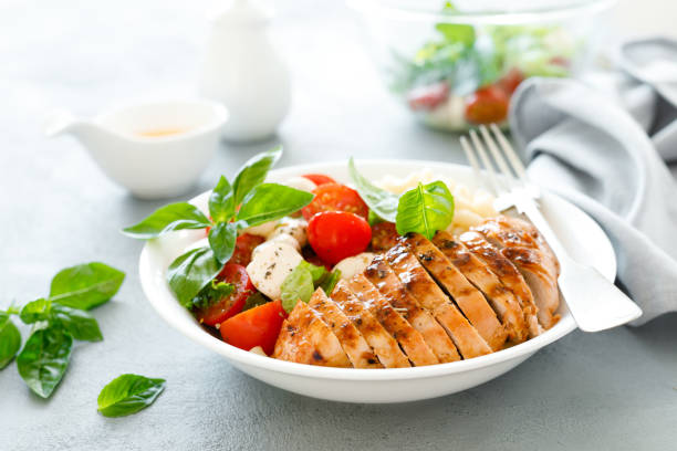 Grilled chicken lunch bowl with orange juice dressing, pasta and caprese salad stock photo