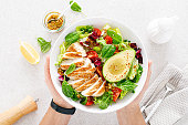 istock Grilled chicken meat and fresh vegetable salad of tomato, avocado, lettuce and spinach. Healthy and detox food concept. Ketogenic diet. Buddha bowl in hands on white background, top view 1295633127