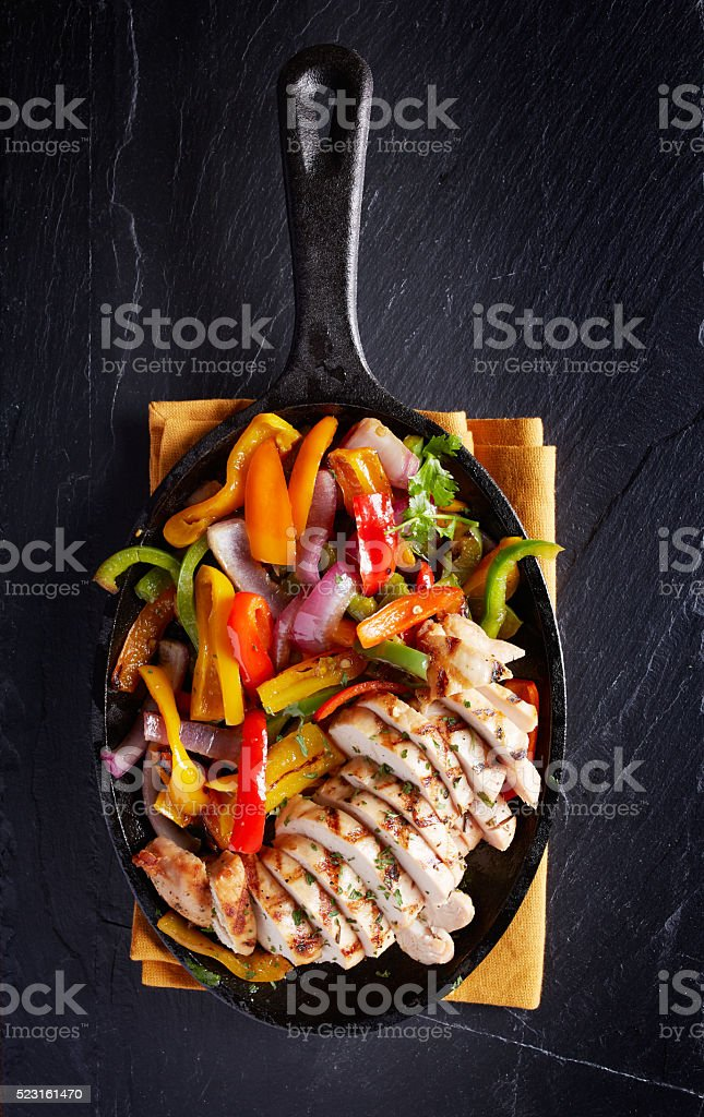 grilled chicken mexican fajitas in iron skillet stock photo