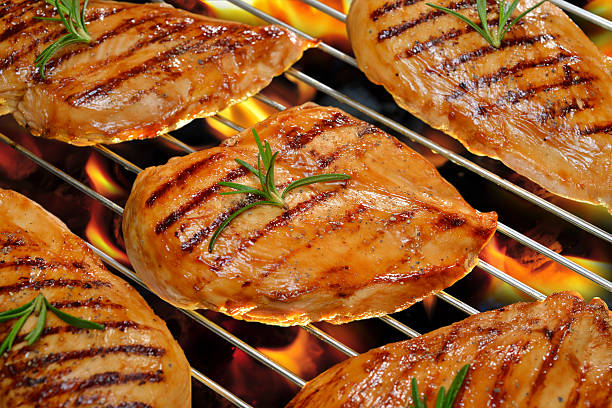 Grilled chicken Grilled chicken breast on the flaming grill. grilled chicken breast stock pictures, royalty-free photos & images