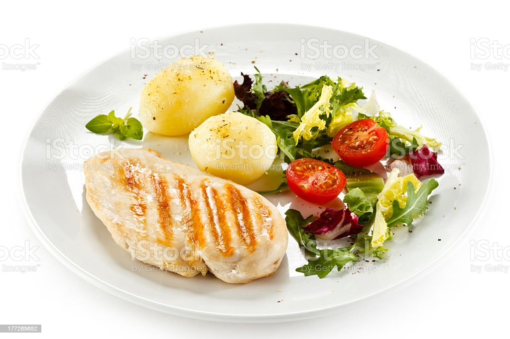 Grilled chicken, potatoes and salad on white plate stock photo